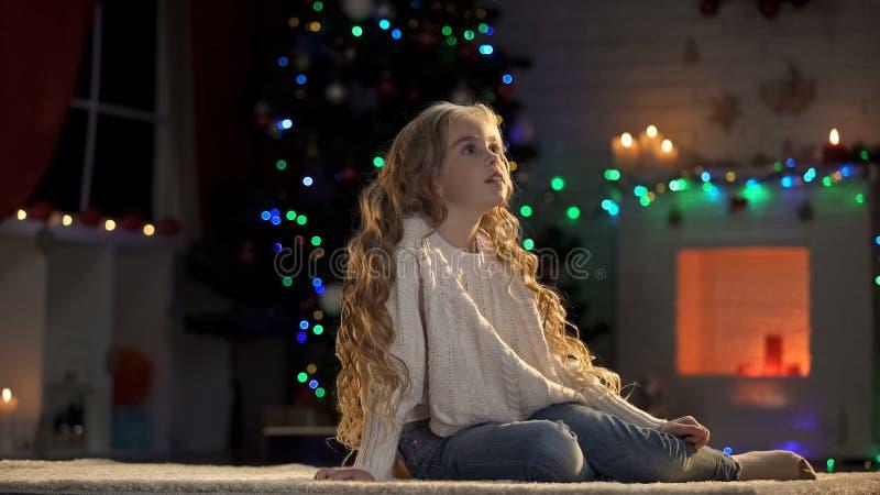 Muchacha que se sienta en piso en el sitio adornado para Navidad, Papá Noel que espera, magia del día de fiesta imágenes de archivo libres de regalías