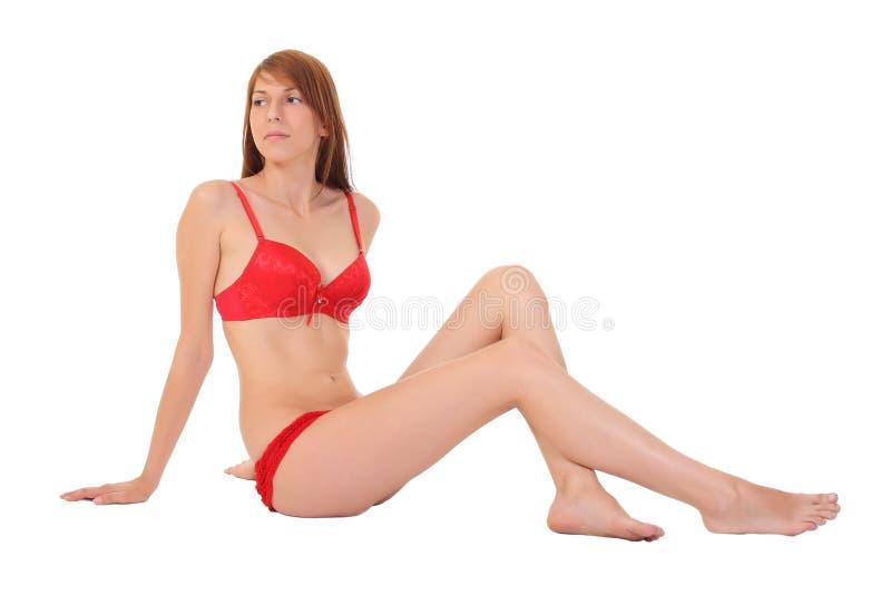 muchacha que se sienta en ropa interior roja foto de archivo