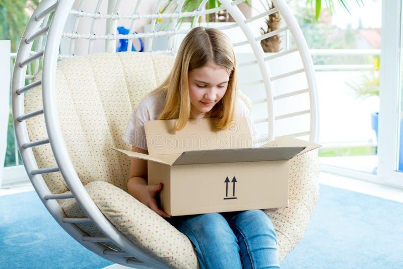Muchacha que se sienta en silla y que abre un paquete imagen de archivo
