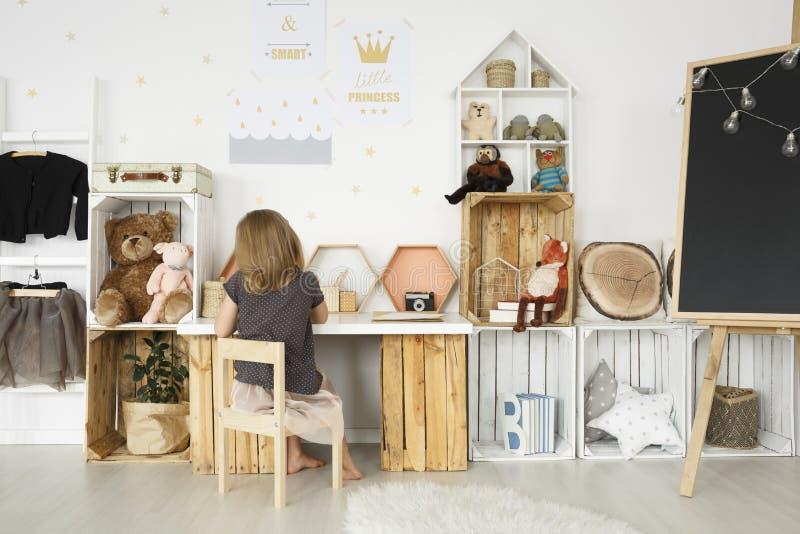 Muchacha que se sienta en su escritorio fotos de archivo