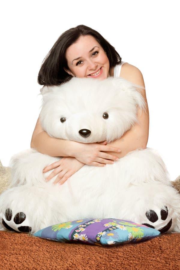 muchacha que se sienta en un abrazo con un oso de peluche imagenes de archivo