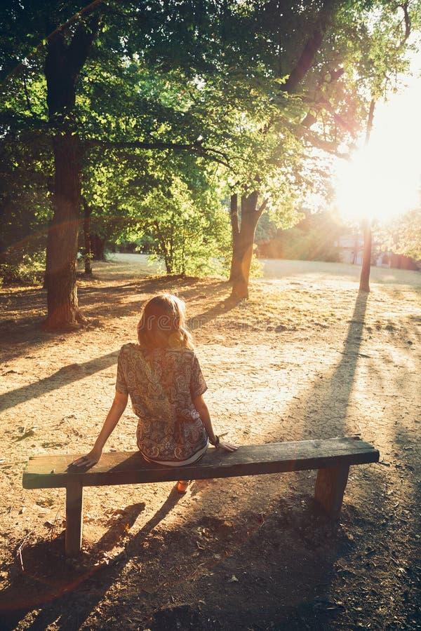 Muchacha que se sienta en un banco de parque imágenes de archivo libres de regalías