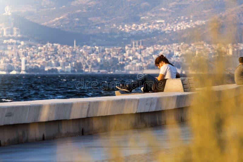 Muchacha que se sienta en un banco en la playa en Esmirna Turquía foto de archivo libre de regalías
