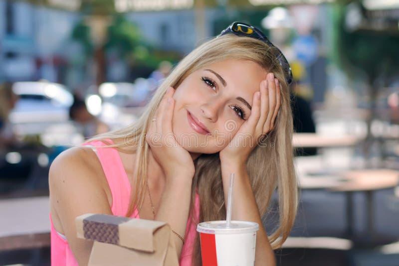Muchacha que se sienta en un café al aire libre y sonrisas fotografía de archivo libre de regalías