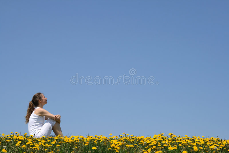 Muchacha que se sienta en un campo fotos de archivo
