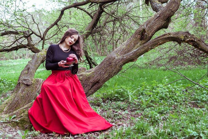 Muchacha que se sienta en un tronco de árbol imagenes de archivo