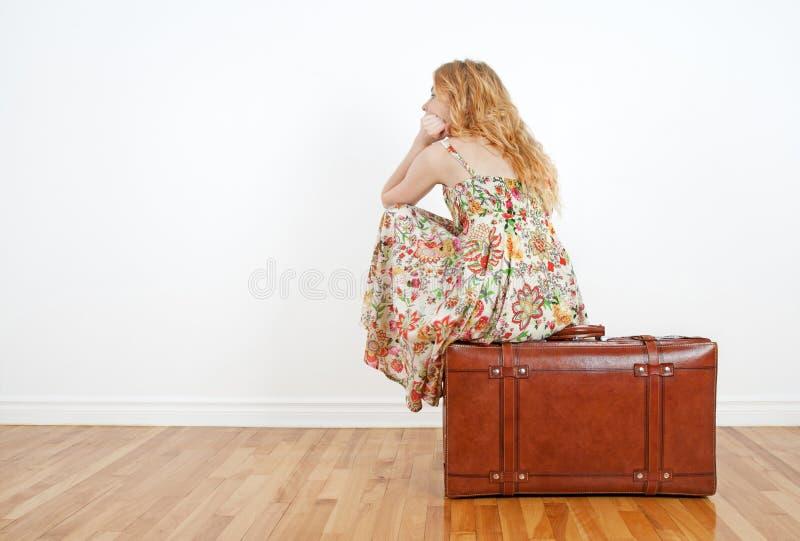 Muchacha que se sienta en una maleta de la vendimia, esperando foto de archivo libre de regalías