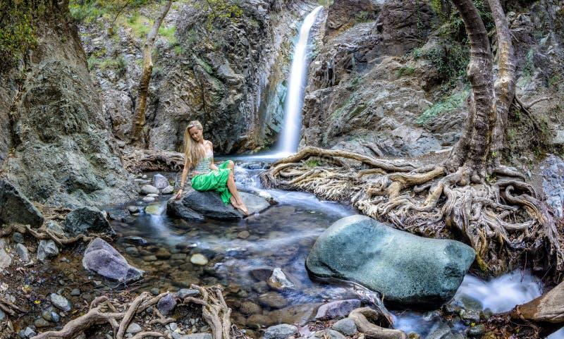 Muchacha que se sienta por las cascadas del millomeri en las montañas de los troodos imagen de archivo