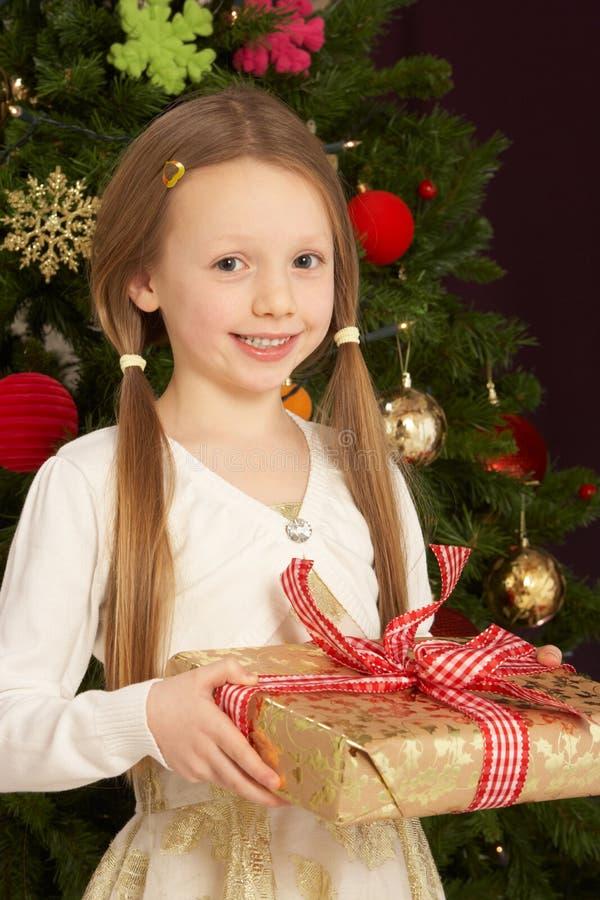 Muchacha que se sostiene presente delante del árbol de navidad fotos de archivo