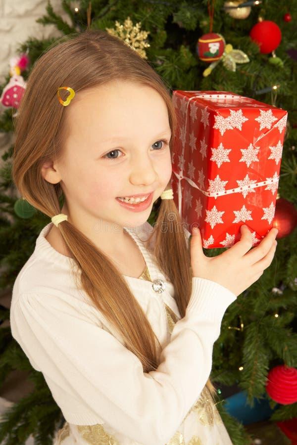 Muchacha que se sostiene presente delante del árbol de navidad foto de archivo