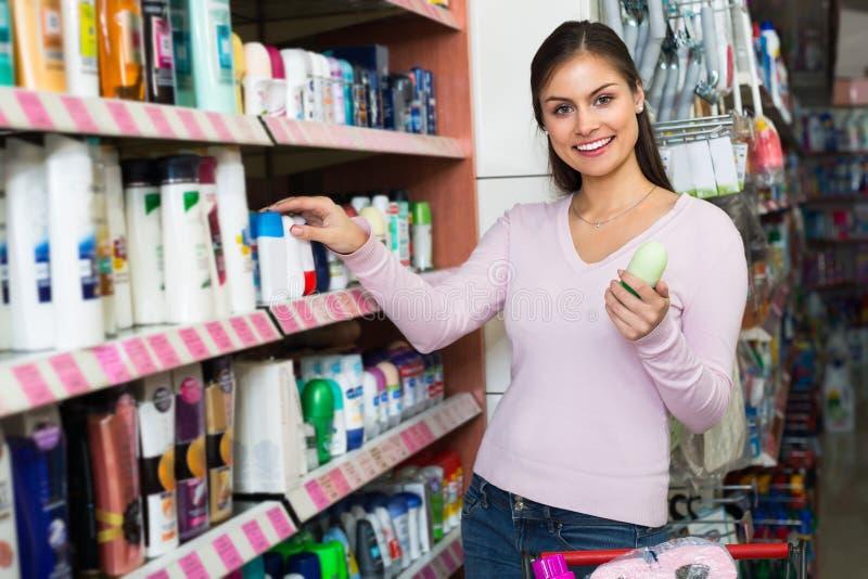 Muchacha que selecciona el desodorante en tienda de los cosméticos foto de archivo libre de regalías
