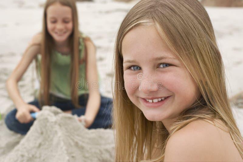 Muchacha que sonríe con la hermana Making Sand Castle en fondo imagen de archivo libre de regalías