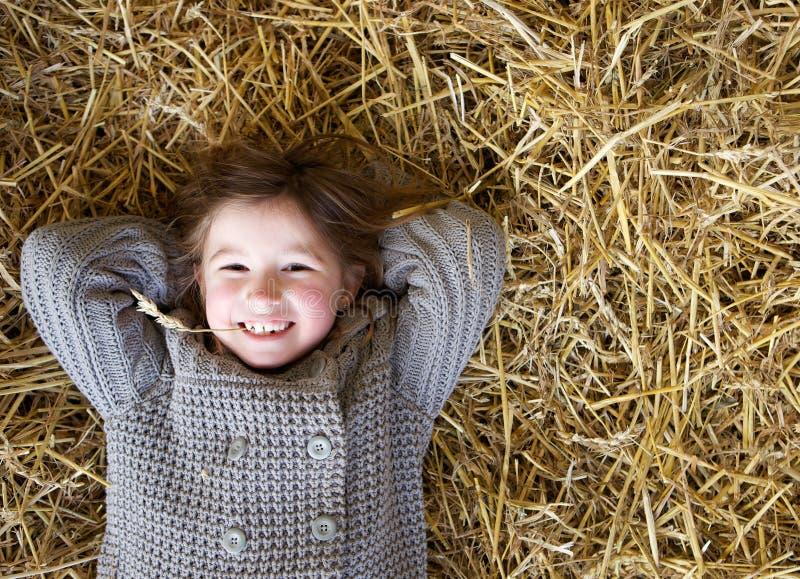 Muchacha que sonríe y que se acuesta en el heno foto de archivo libre de regalías
