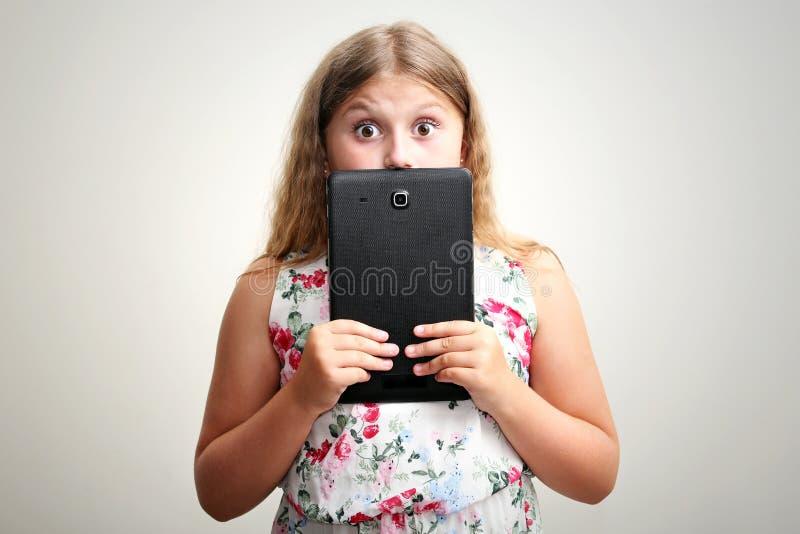 Muchacha que sonríe y sorprendida con la tableta fotografía de archivo