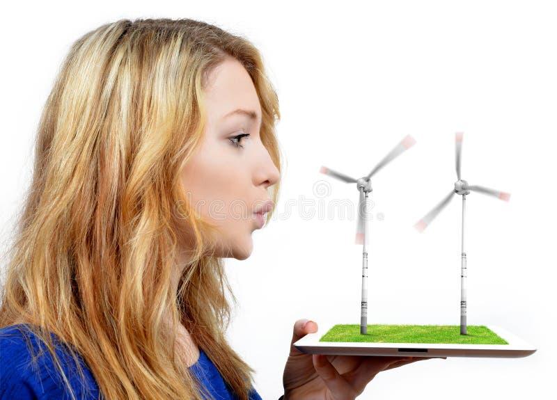 Muchacha que sopla en las turbinas de viento imagen de archivo