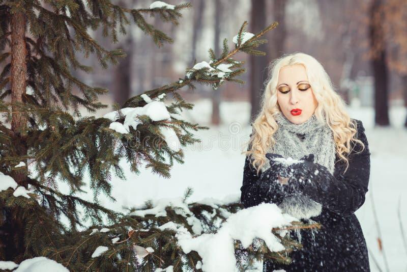 Muchacha que sopla en nieve en manos imagen de archivo