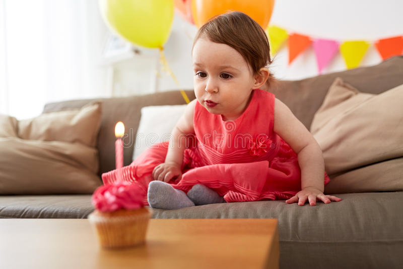 Muchacha que sopla a la vela en la magdalena del cumpleaños en casa fotografía de archivo libre de regalías