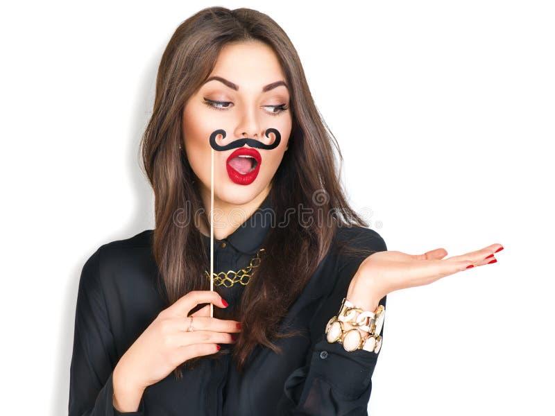 Muchacha que sostiene el bigote divertido en el palillo y que muestra el copyspace vacío imagen de archivo libre de regalías