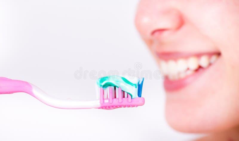 Muchacha que sostiene el cepillo de dientes con goma fotos de archivo