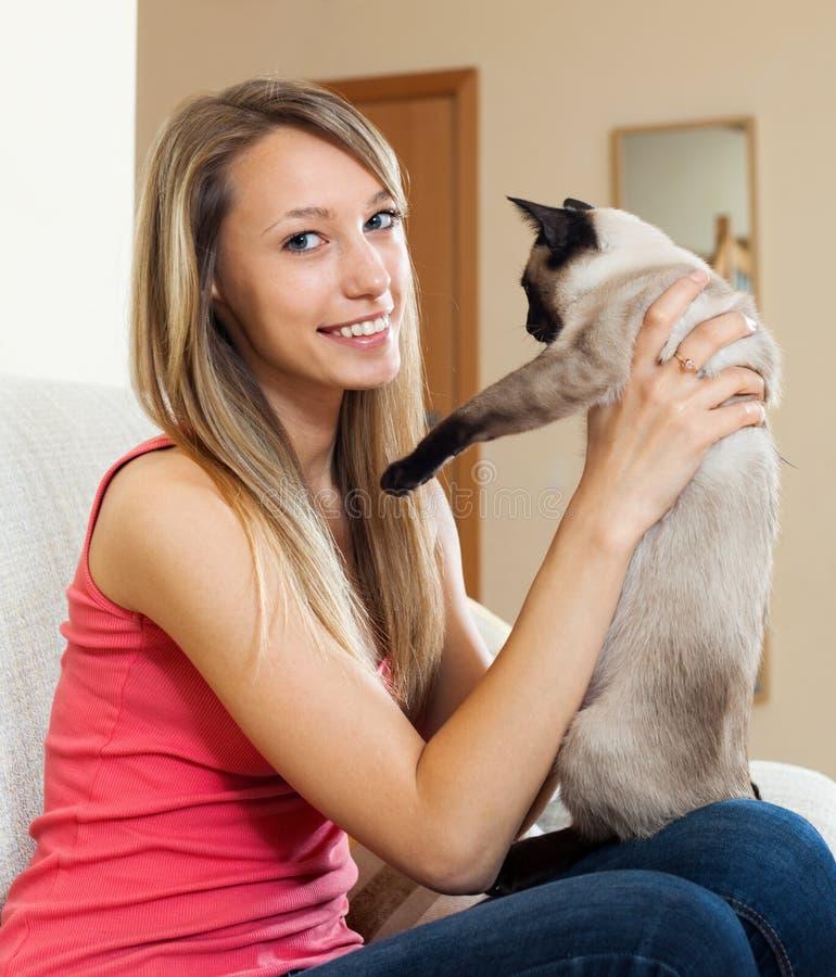 Muchacha que sostiene el gatito siamés en brazos fotografía de archivo