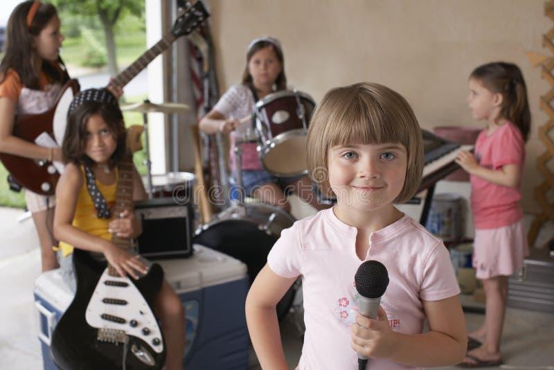 Muchacha que sostiene el micrófono con los amigos que tocan el instrumento musical imagenes de archivo