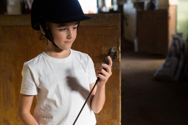Muchacha que sostiene el palillo de la cosecha en establo fotos de archivo libres de regalías