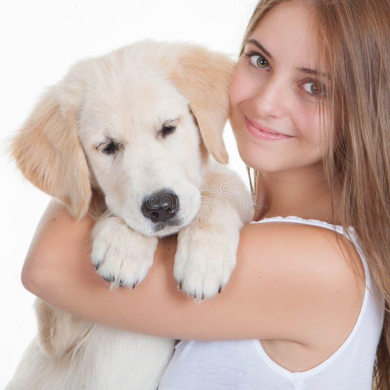 Muchacha que sostiene el perrito de Labrador del animal doméstico foto de archivo