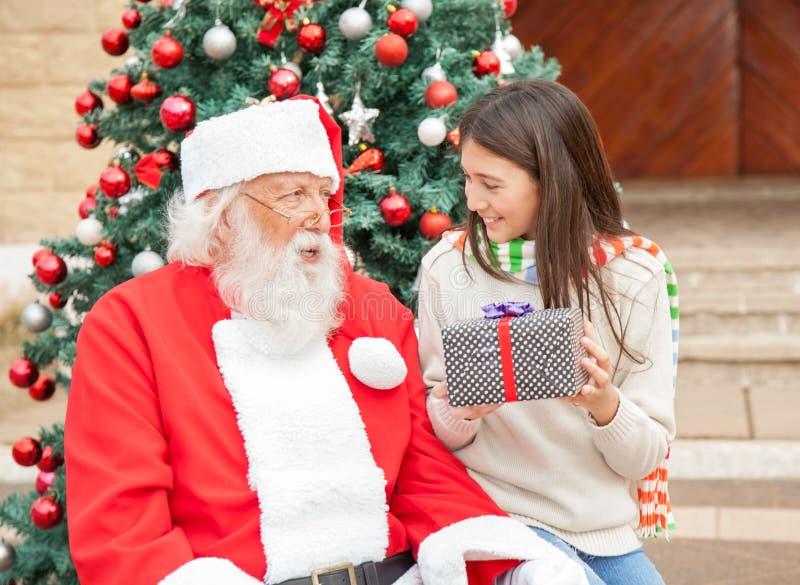 Muchacha que sostiene el regalo mientras que mira a Santa Claus imagen de archivo libre de regalías