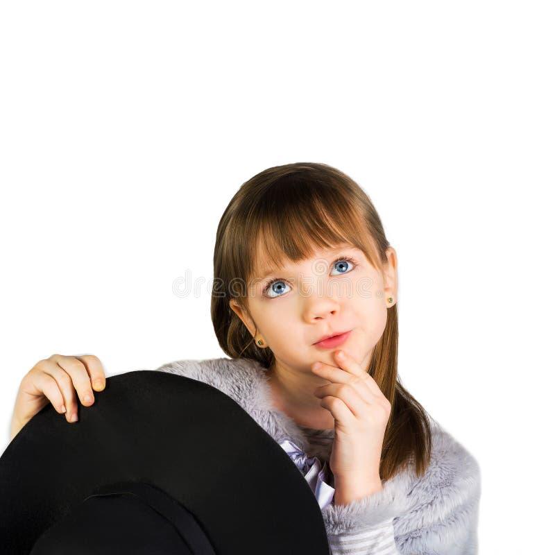 Muchacha que sostiene el sombrero y ojos grandes fotografía de archivo libre de regalías