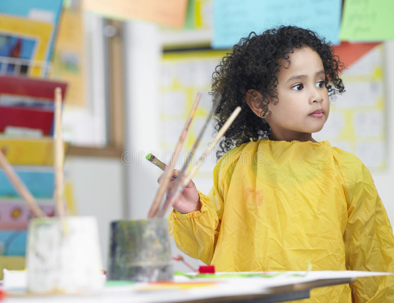 Muchacha que sostiene la brocha en Art Class imagen de archivo libre de regalías