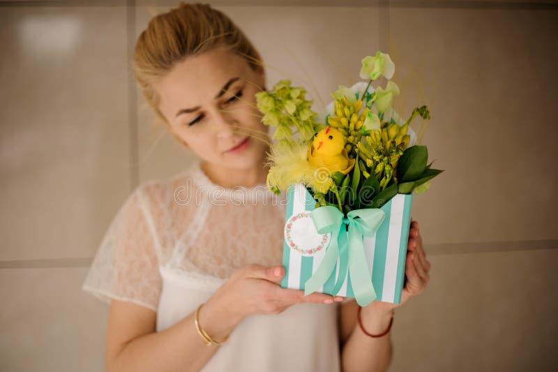 Muchacha que sostiene la caja rayada del sombrero con las flores fotos de archivo