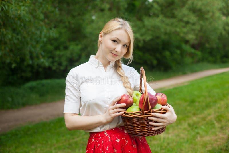 Download Muchacha Que Sostiene La Cesta Con Las Manzanas Rojas Y Verdes En El Parque Imagen de archivo - Imagen de camisa, ropas: 41907177