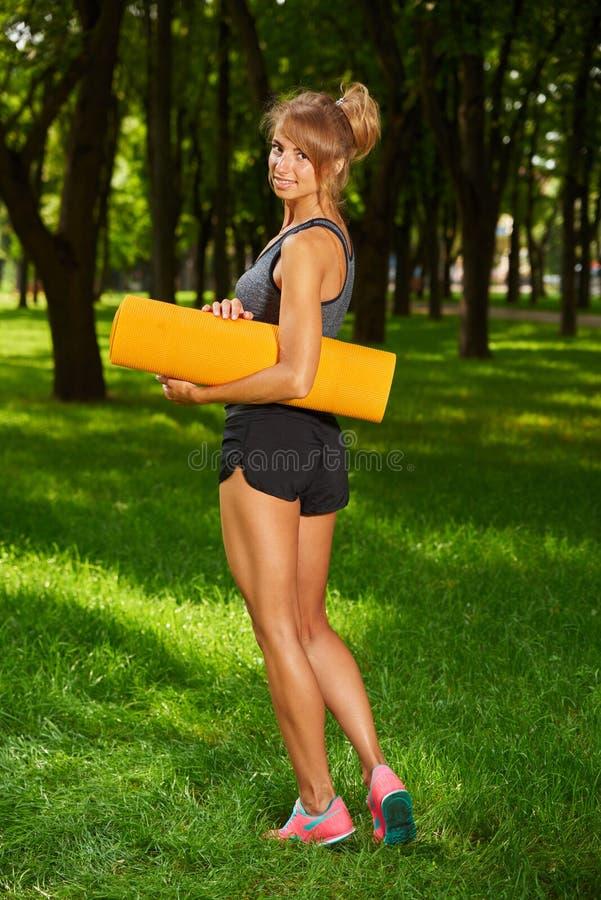 Muchacha que sostiene la estera de la yoga en las manos que se colocan en parque imagen de archivo