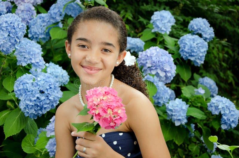 Muchacha que sostiene la flor rosada imagenes de archivo