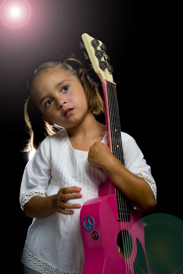 Muchacha que sostiene la guitarra en etapa imágenes de archivo libres de regalías