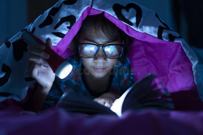 Muchacha que sostiene la linterna mientras que manta de los libros de lectura de los vidrios del desgaste en sitio de la cama imagen de archivo