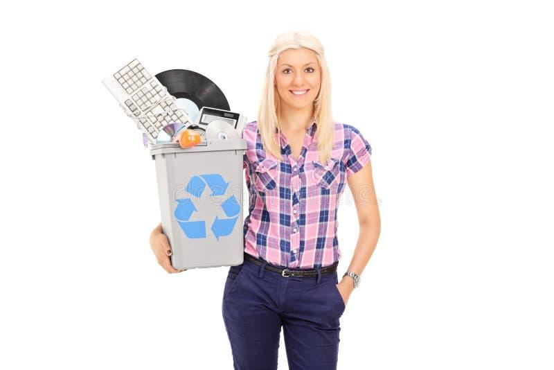 Muchacha que sostiene la papelera de reciclaje llena de accesorios viejos imagen de archivo
