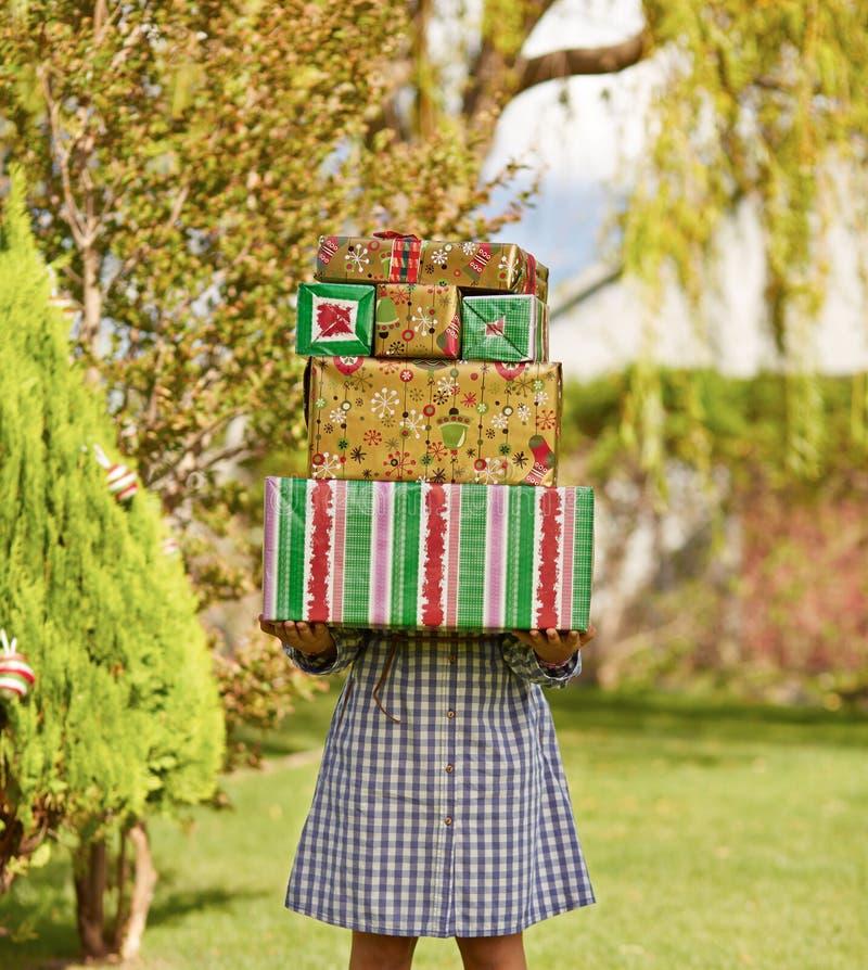 Muchacha que sostiene la pila de regalos de Navidad fotografía de archivo libre de regalías