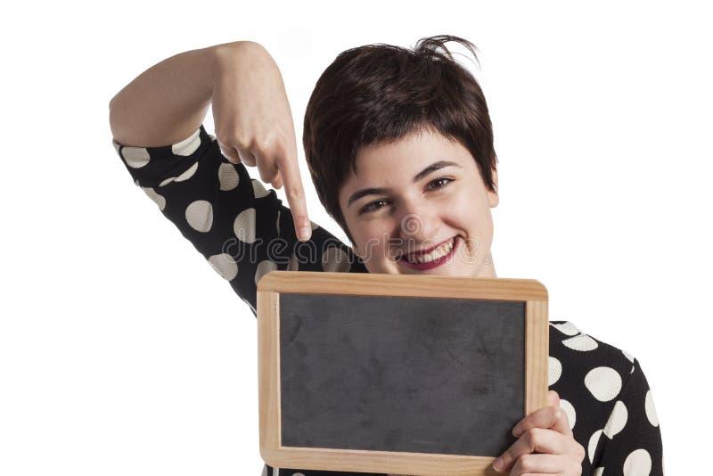 Muchacha que sostiene la pizarra en blanco en blanco fotografía de archivo libre de regalías