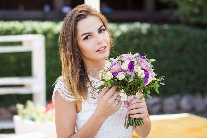 Muchacha que sostiene las flores en las manos, novia hermosa joven en el vestido blanco que sostiene el ramo de la boda, ramo de  fotos de archivo