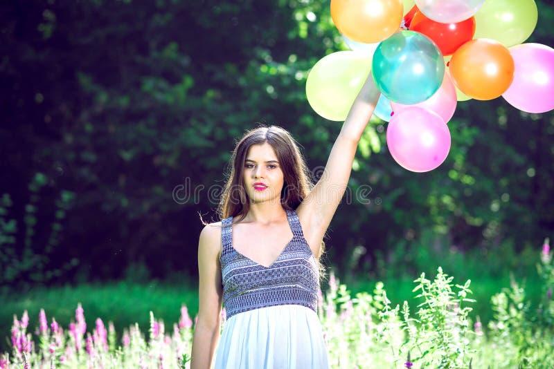 Muchacha que sostiene los globos disponibles fotos de archivo