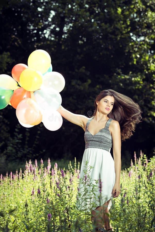Muchacha que sostiene los globos disponibles imágenes de archivo libres de regalías