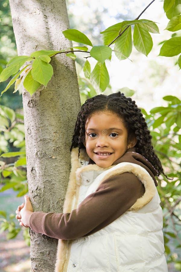 Muchacha que sostiene un árbol imagenes de archivo