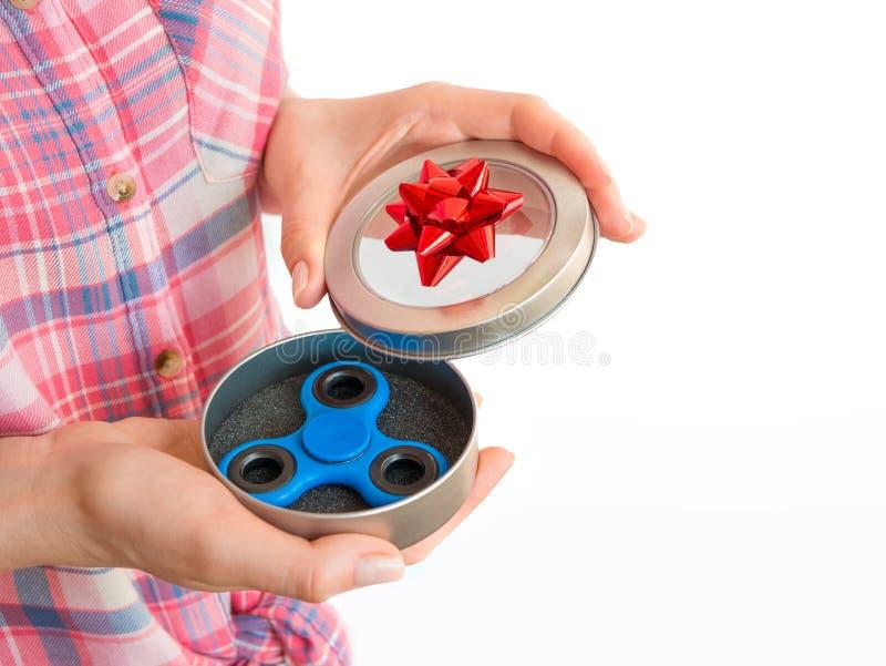 Muchacha que sostiene un juguete colorido del hilandero de la persona agitada de la mano en una caja de regalo fotografía de archivo