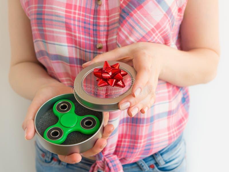 Muchacha que sostiene un juguete colorido del hilandero de la persona agitada de la mano en una caja de regalo fotografía de archivo libre de regalías