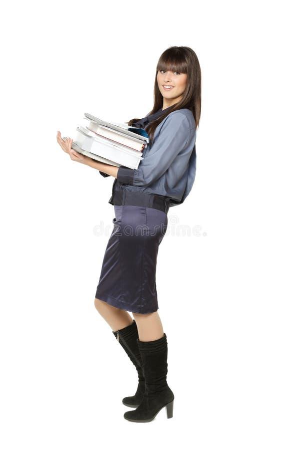 Muchacha que sostiene un montón de libros imagenes de archivo