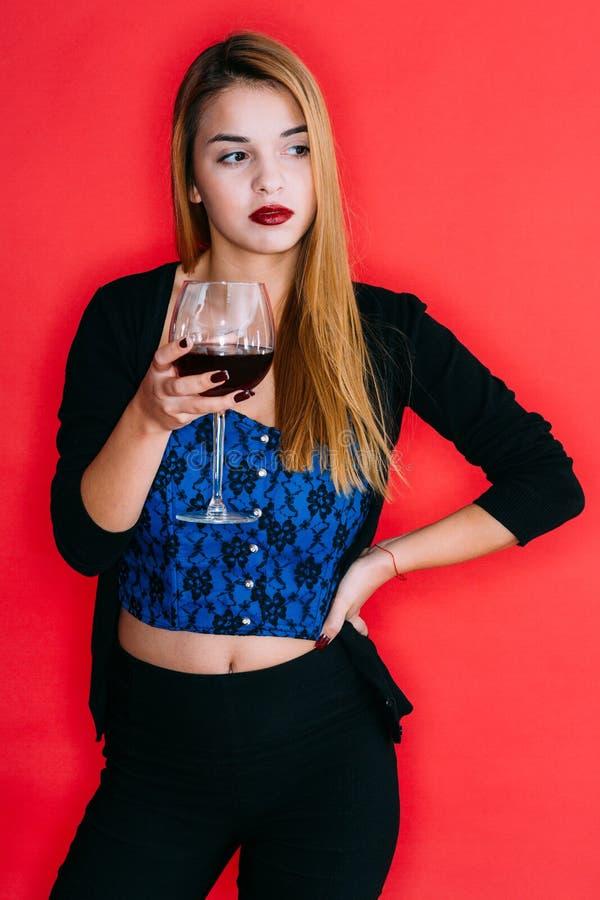 Muchacha que sostiene un vidrio de vino rojo foto de archivo libre de regalías