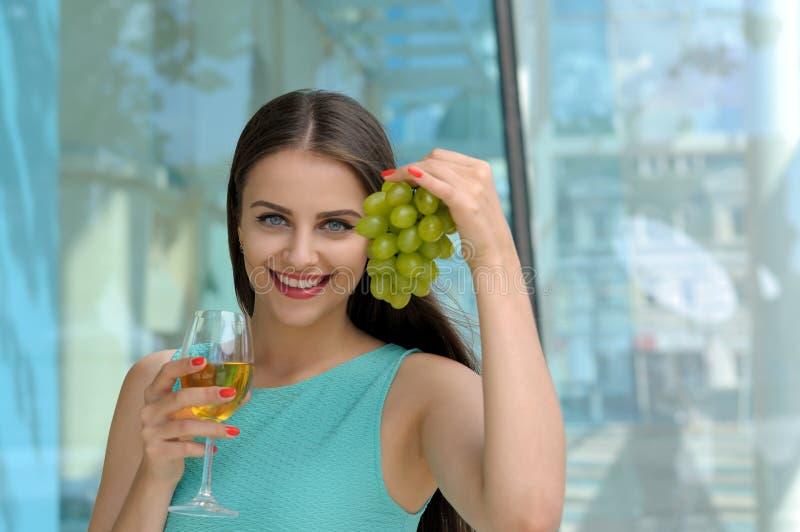 Muchacha que sostiene un vidrio lleno de vino blanco en su mano derecha fotos de archivo libres de regalías