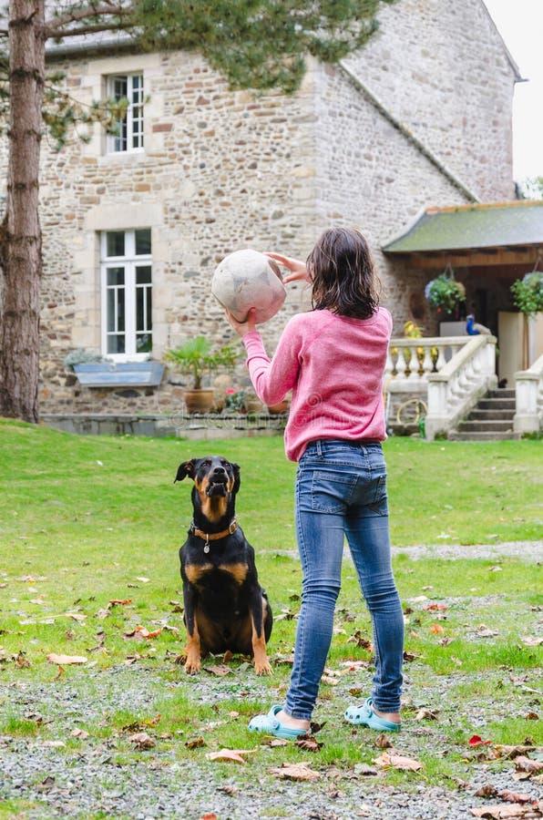 Muchacha que sostiene una bola y que juega con el perro negro imagenes de archivo