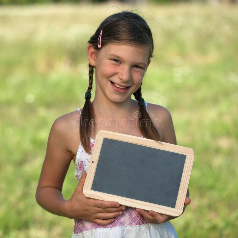 Muchacha que sostiene una pequeña pizarra foto de archivo